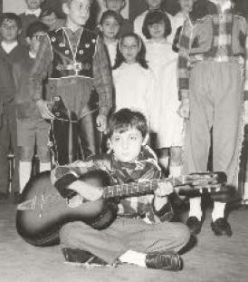 Tino Carugati da piccolo che fa musica con la chitarra